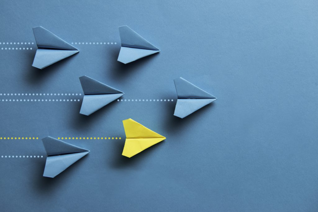 Image of paper planes flying in one direction with one yellow plane standing out to showcase distinction
